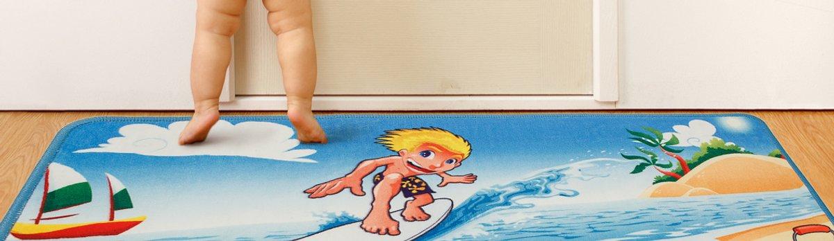 Babybeine auf einer bedruckten Foto-Fußmatte mit Surfer-Motiv
