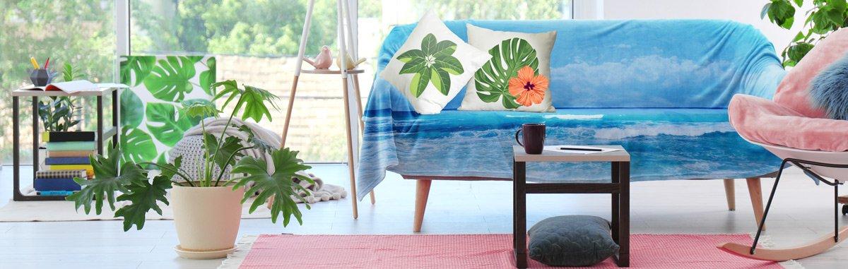 Stylisches Sofa mit maritimer Tagesdecke und Kissen mit angesagtem Palmenblätter-Motiven