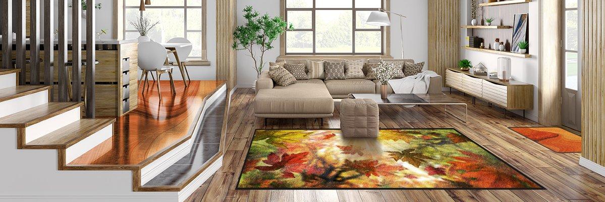 Modernes Wohnzimmer in Holzoptik. Auf dem Boden vor der Couch ein Teppich mit Herbstmotiv
