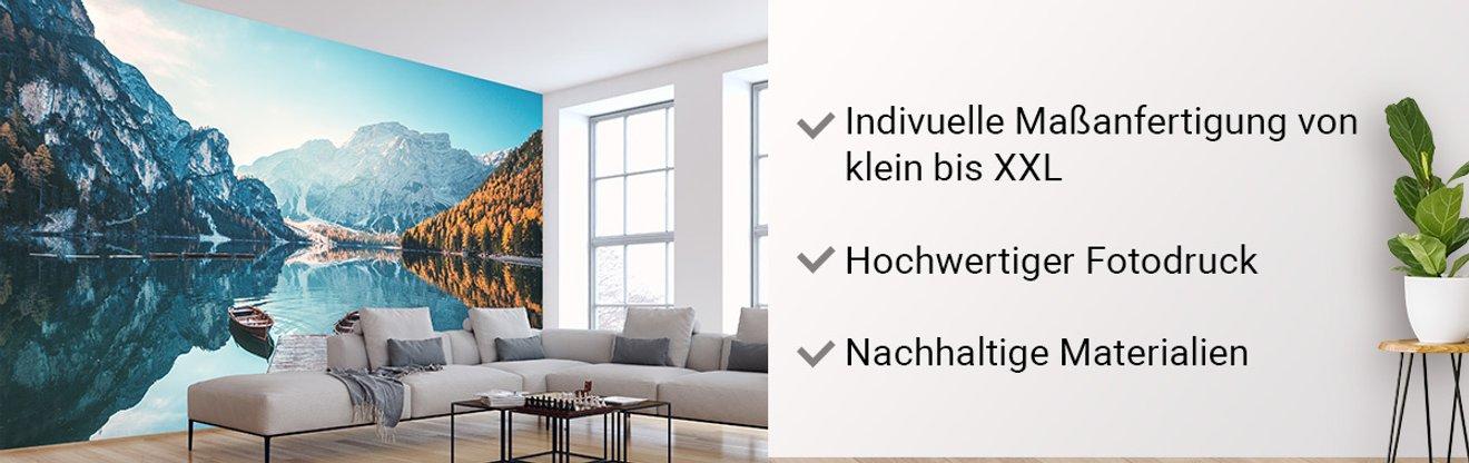 Header image mit einer großen Fototapete im modernen, gellen Wohnzimmer. Auf der Tapete ein Bersee mit Bergen drum herum.